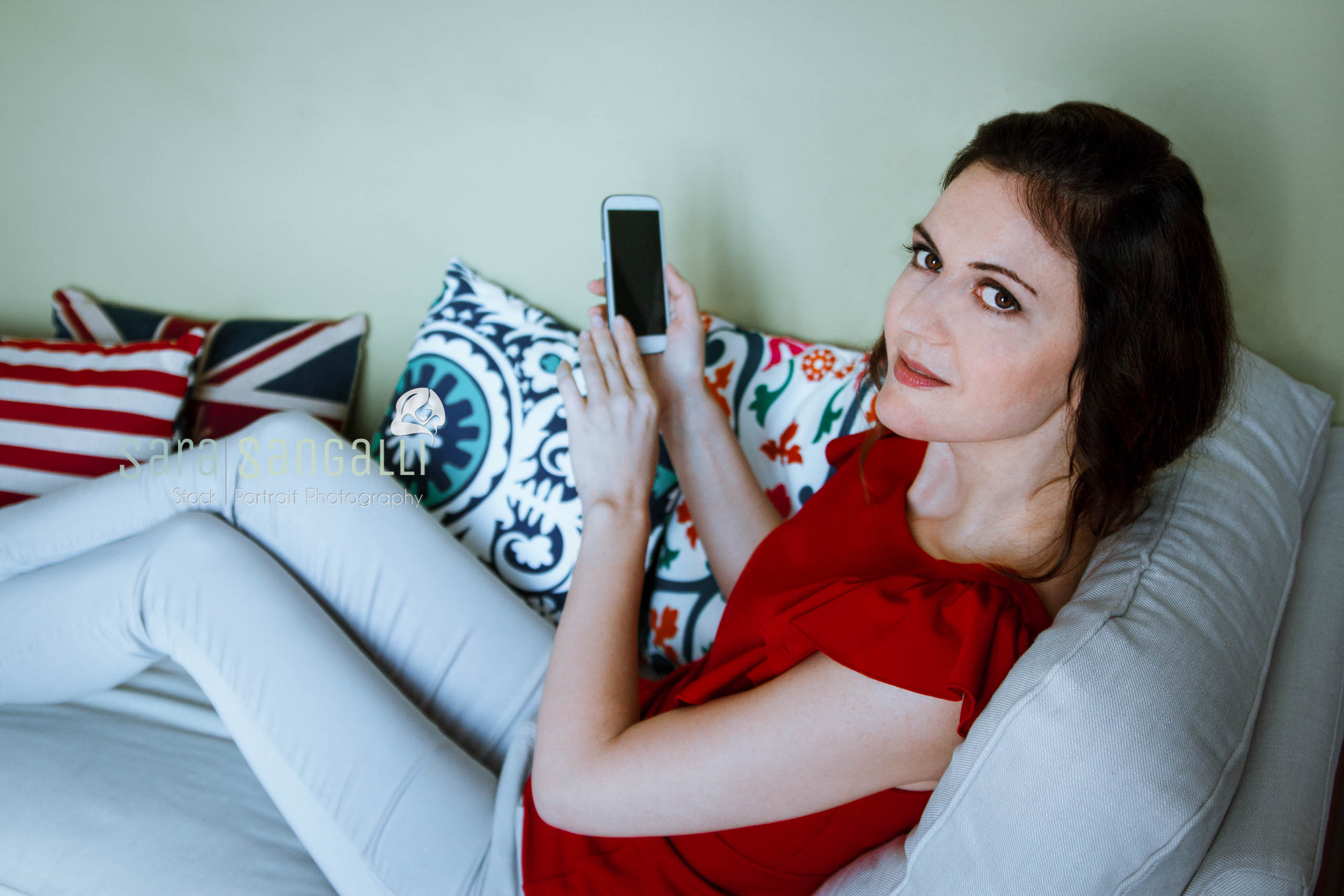 Brunette holding smartphone while sitting on a couch and looking at camera