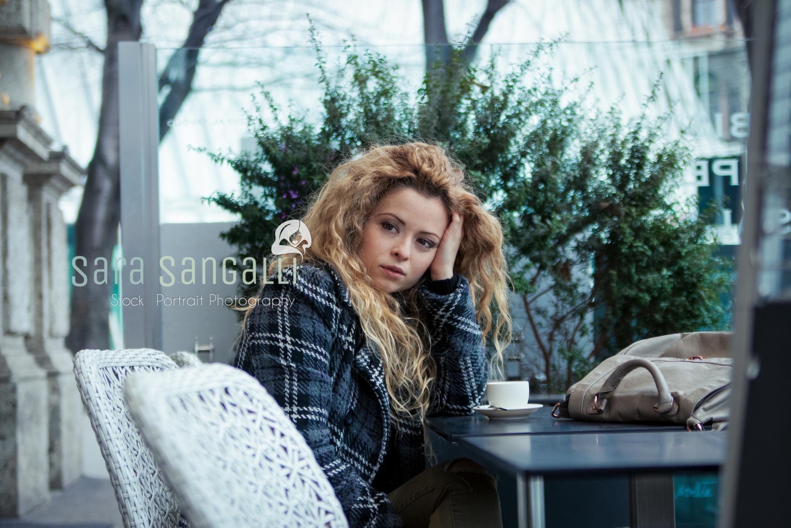 Young blonde woman taking a break at a coffee bar. Serious expression, looking away.