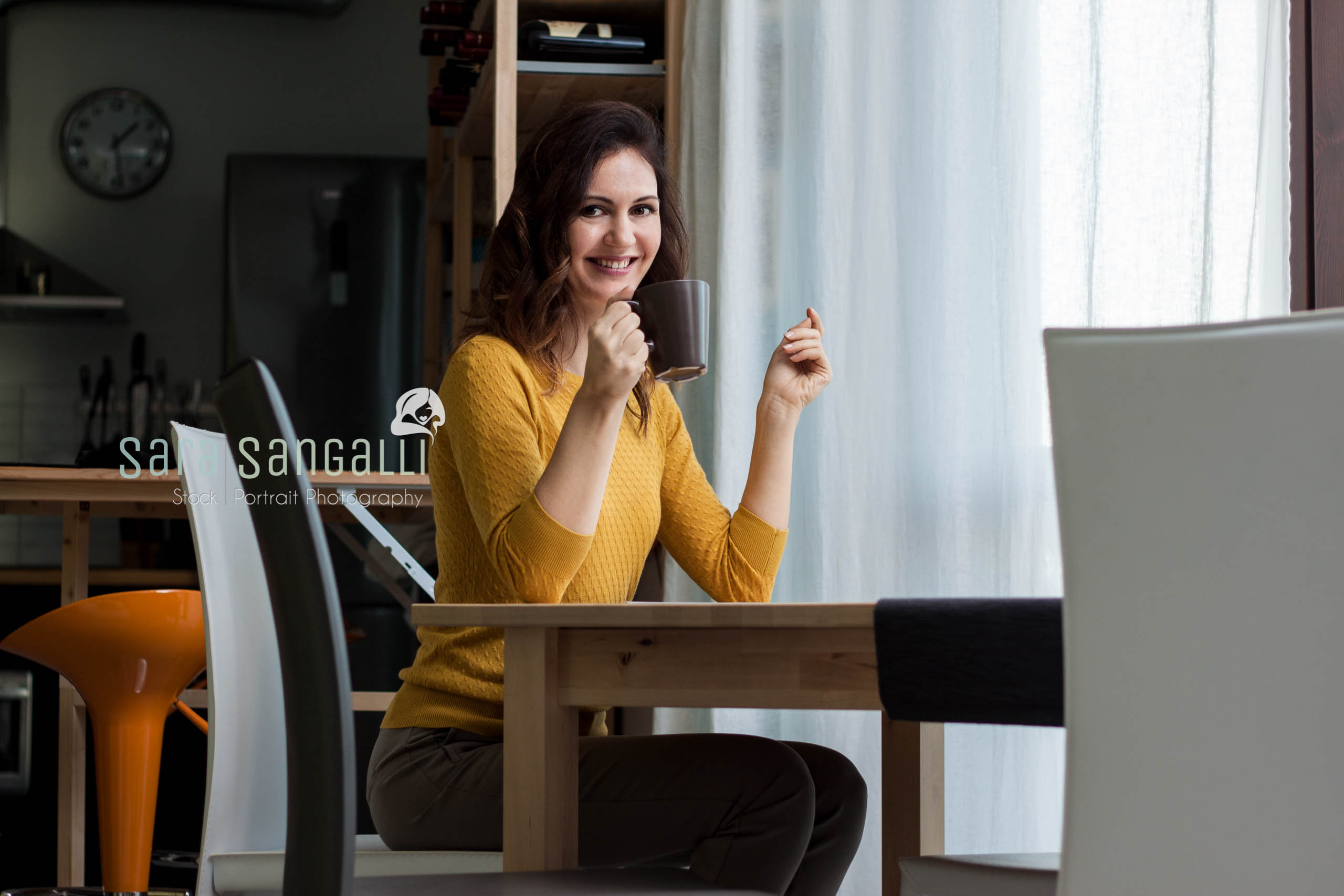 Young caucasian brunette woman drinking from a cup, sitting near a table. Indoor setting