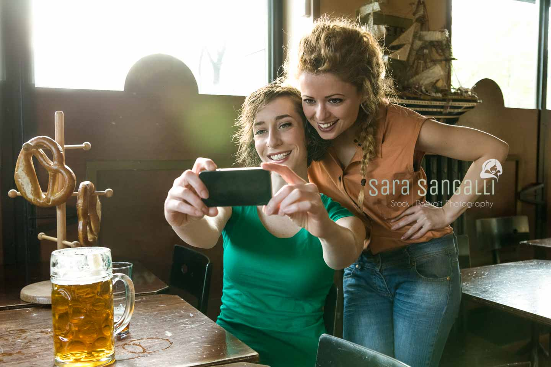 Two girlfriends taking a selfie inside a pub