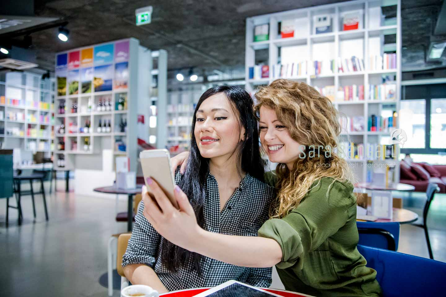 Two young women of caucasian and chinese ethnicity take a selfie inside a design studio