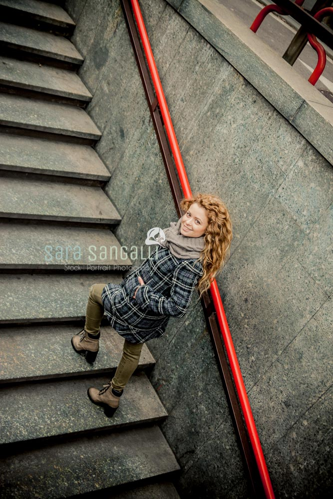 Young blonde woman walking up the stairs of one of Milan metro stations.