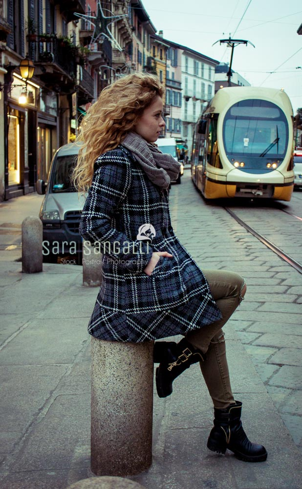 Blonde young woman in Milan, Italy, looking away from camera. Public transportation approaching from behind
