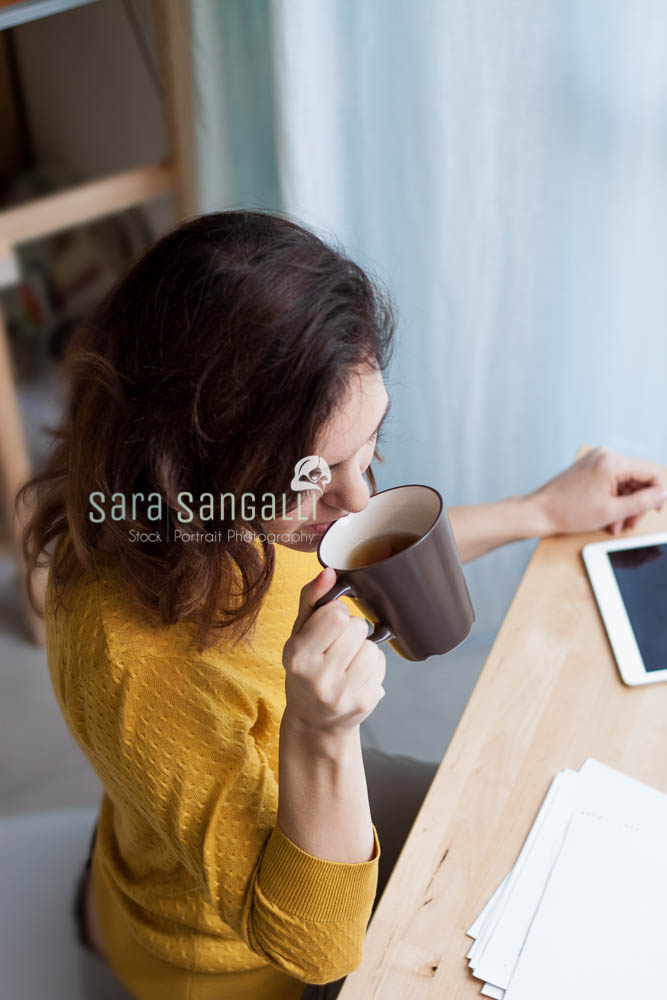 Young caucasian brunette woman taking notes and drinking tea. Indoor setting