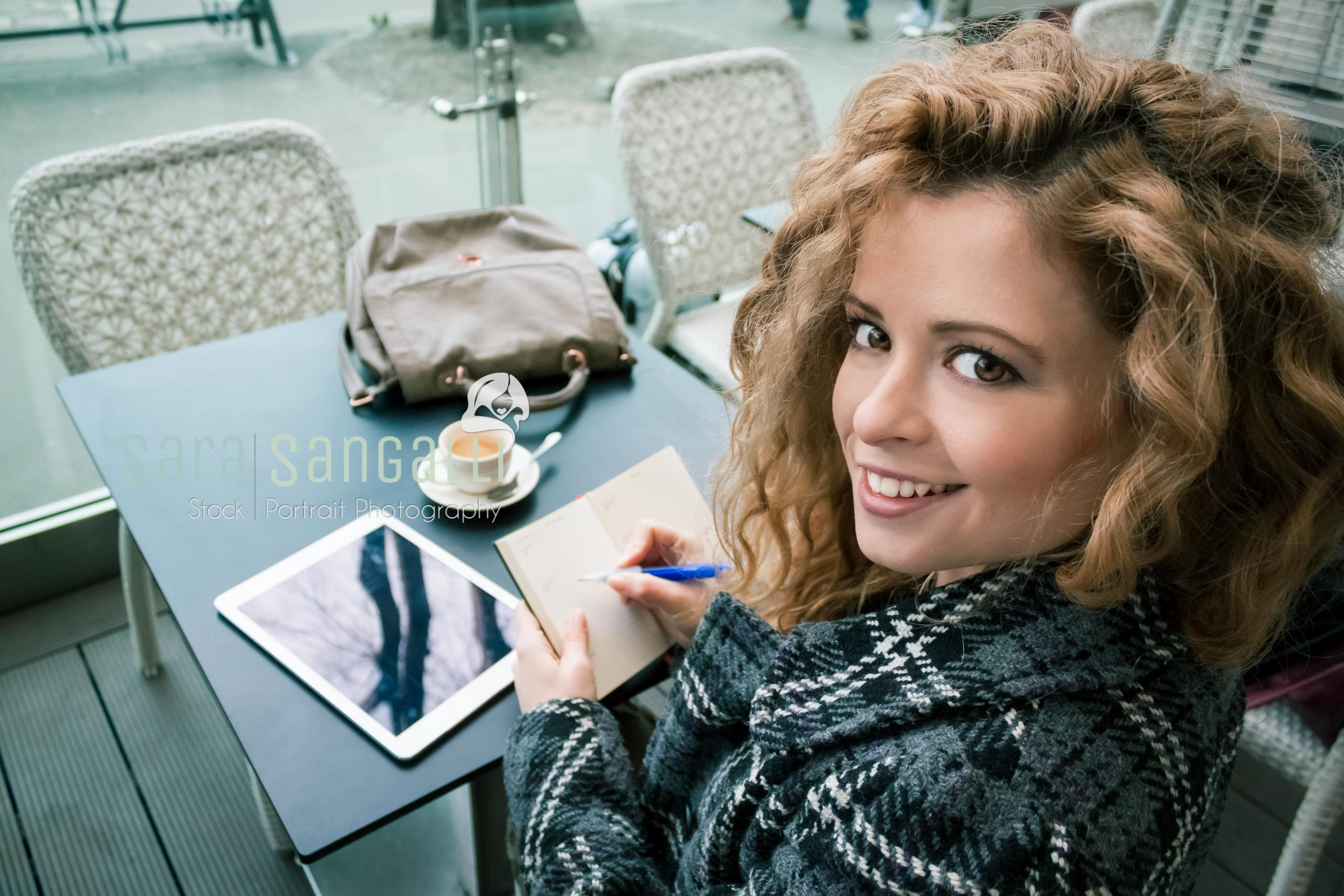 Young blonde woman taking a break at a coffee bar. Taking notes on a tablet and writing on her calendar