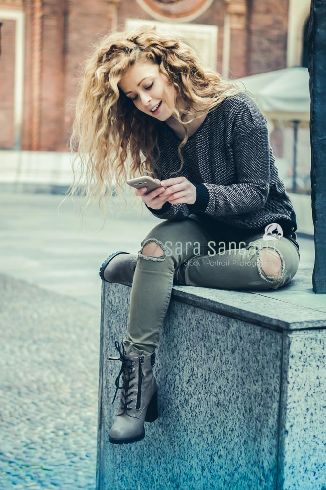 young blonde woman texting on her smartphone