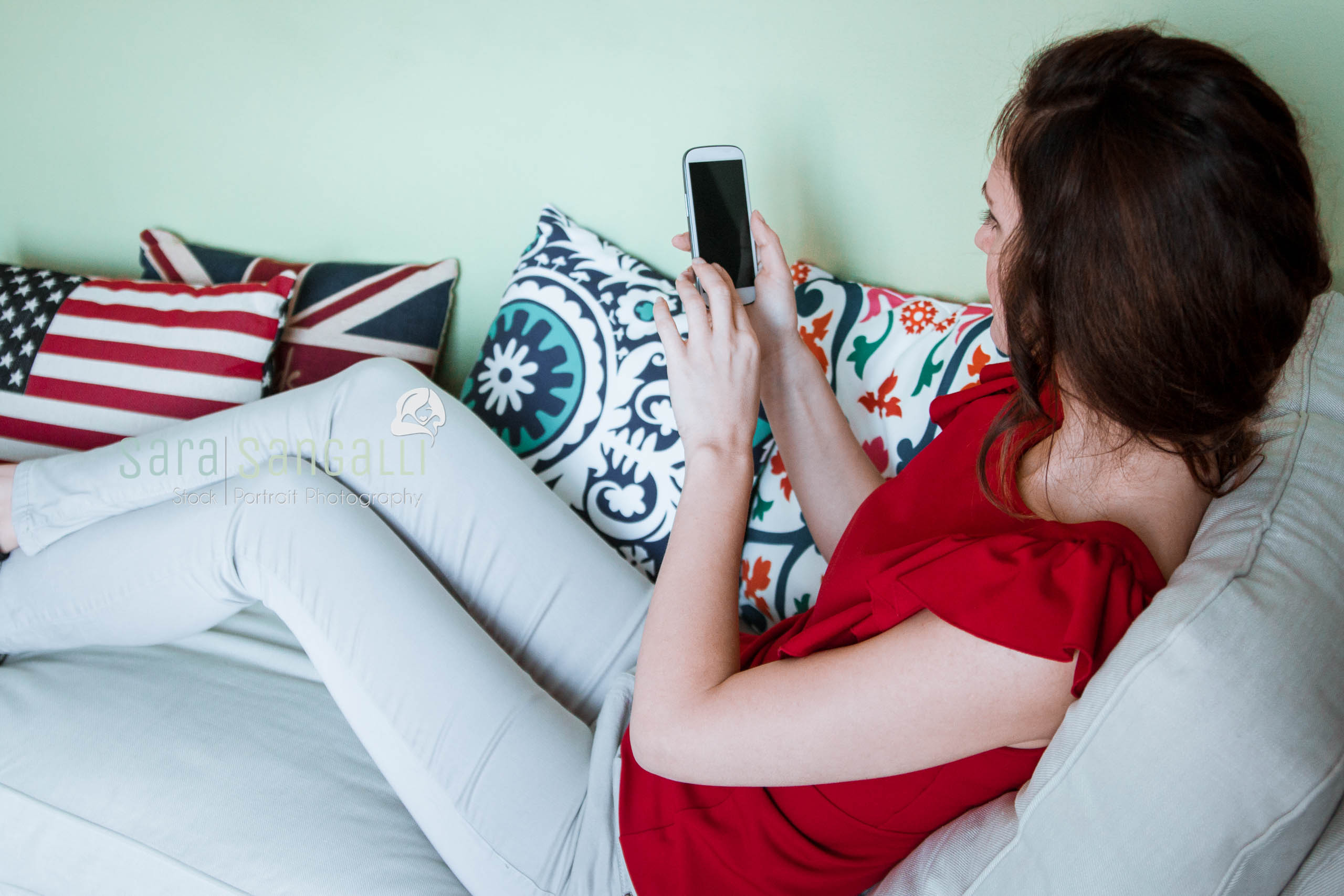 Brunette holding smartphone while sitting on a couch