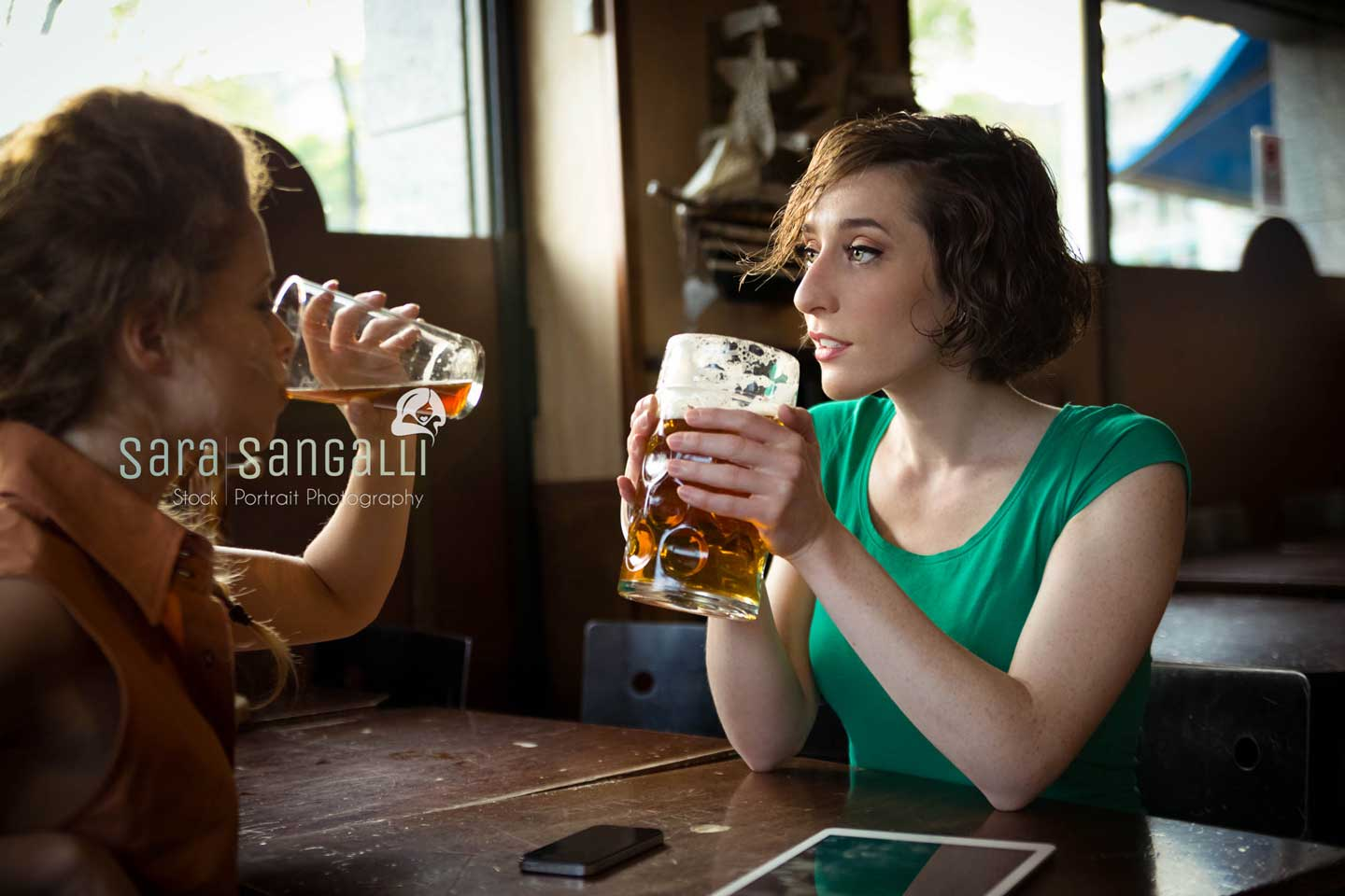 Two girls sitting at a pub table and drinking beer together