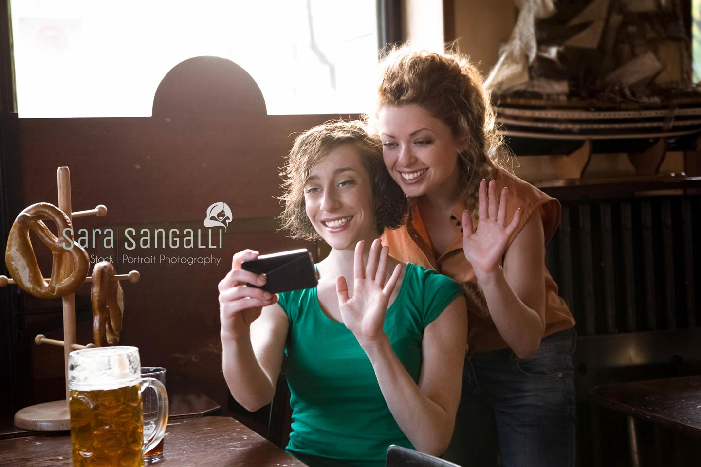Two girlfriend waving at their smartphone