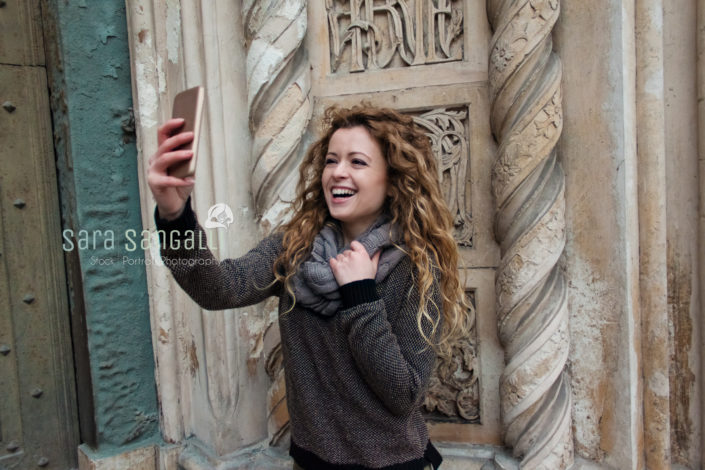 Young blonde girl taking a selfie in front of an ancient building