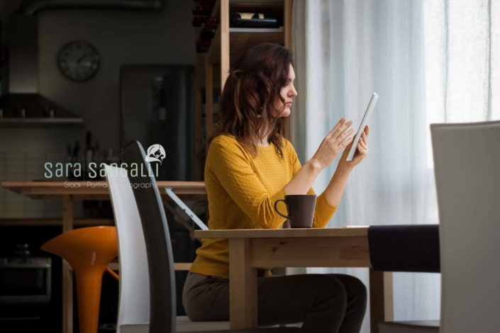 Young caucasian brunette woman using a tablet and sitting near a table. Indoor setting