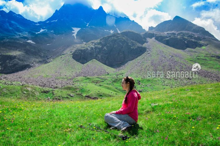 Woman sitting on the grass after a long walk in the mountains