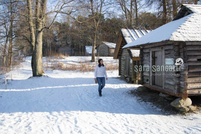 young tourist walking around a reproduction of woodeen villanges at the Estonian Open Air Museum in Tallinn