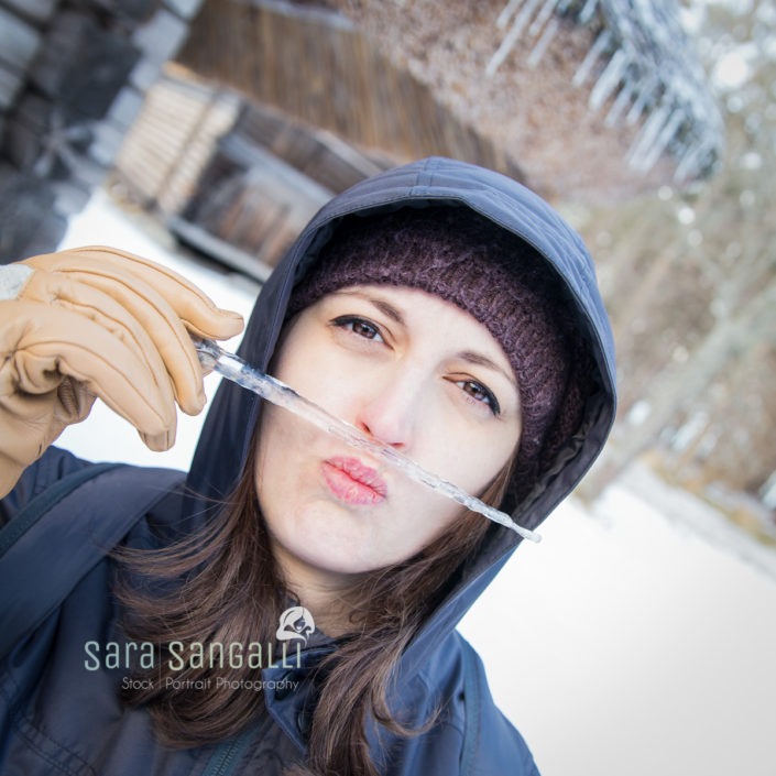 Woman using icicles to make mustaches and funny face